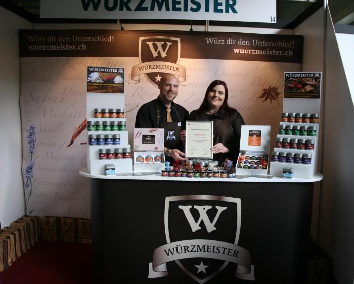 Bild zum Beitrag Würzmeister gewinnt den Jungunternehmerpreis Kloten 2014. Yves und Tania präsentieren den Preis hinter dem Stand.
