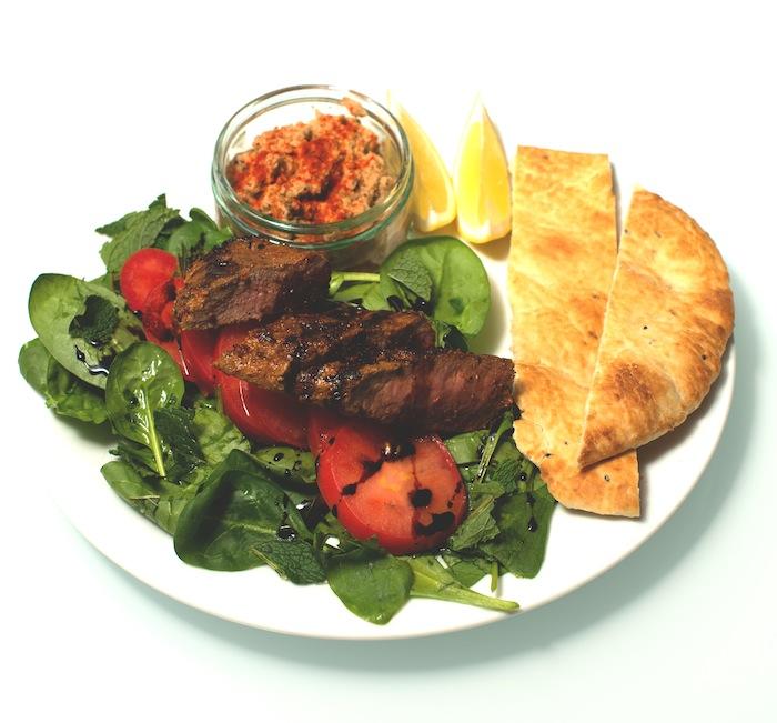 Harissa Lamm mit Baba Ganoush an Spinat und Tomaten Salat mit Naan Brot