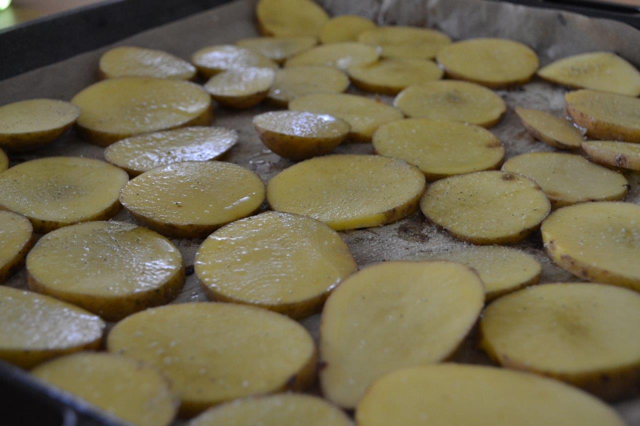 Bild zum Rezept Kartoffeln mit Rosmarin-Knoblauch Salz. Gesalzene und geschnittene Chips bereit für den Ofen.
